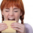 Girl biting piece of cheese — Stock Photo