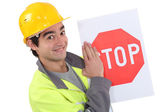 A young road worker holding a stop sign. — Stock Photo