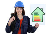 A female electrician promoting energy savings. — Stock Photo