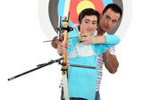 Man and a teenager practicing archery — Stock Photo