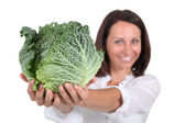Woman presenting a savoy cabbage — Stock Photo