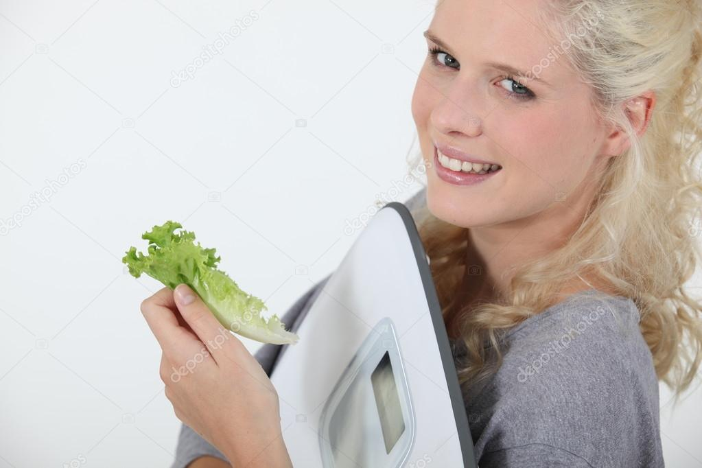 Portrait of angel-faced blonde carrying scales with salad leaf in hand — Stock Photo #14939019