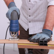 Stock Photo: Carpenter cutting wood with electric saw