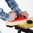 Stock Photo: Tradesmusing plane to smooth plank of wood
