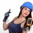 Sexy tradeswoman holding a multimeter — Stock Photo