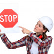 Female laborer pointing stop sign - Stock Photo