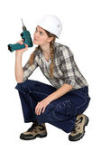 Handywoman crouching with drill — Stock Photo