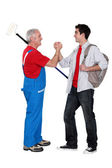 A mature painter shaking hand with his trainee. — Stock Photo