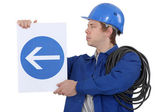 Electrician with a road sign — Stock Photo