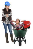 Craftswoman accusing her lazy colleague for sitting in a wheelbarrow — Stock Photo