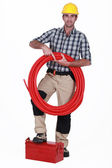 Tradesman holding corrugated tubing and propping his foot on a toolbox — Stock Photo