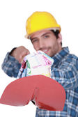 Laborer with a shovel full of bills — Stock Photo