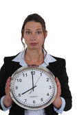 Businesswoman with a clock showing 8am — Stock Photo