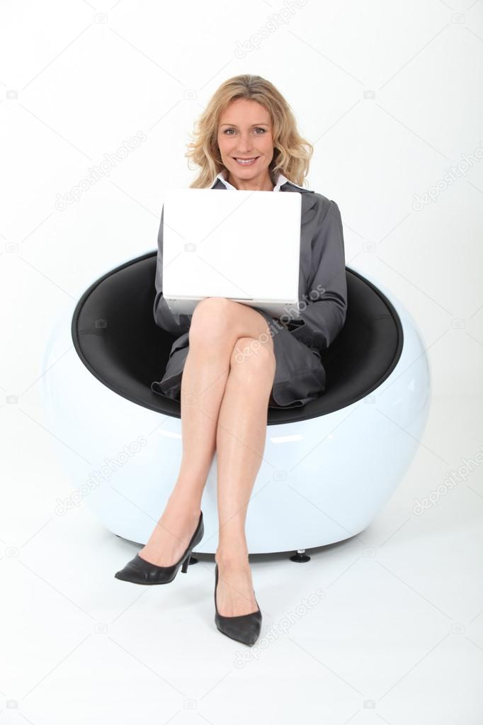 Mature director sitting in an armchair with laptop stock for Sitting in armchair