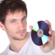 Young man showing CD, studio shot - Stock Photo