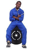Mechanic sitting on a wheel — Stock Photo