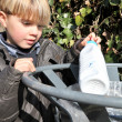 Stock Photo: Boy putting rubbish in park bin