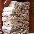 Snowy log pile outside a cabin - Stock Photo