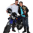 Stock Photo: Father and son with motorcycle and trophy