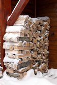 Snowy log pile outside a cabin — Stock Photo