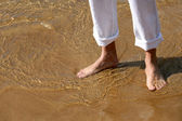 Close-up of barefoot walking on the sand — Stock Photo