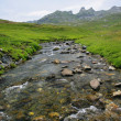 Stream running along mountain top - Stock Photo