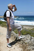 Mature backpacker gazing at the ocean — Stockfoto
