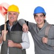 Experienced tradesman posing with his new apprentice — Stock Photo #15622527