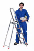 Man stood by ladder holding selection of wallpaper rolls — Stock Photo