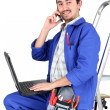 Stock Photo: Plumber sat on step ladder holding mobile telephone
