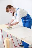 Female DIY enthusiast wallpapering — Stock Photo