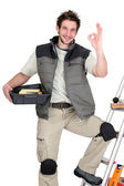 Approving tile fitter posing with his tools and building materials — Stock Photo