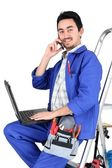 Plumber sat on step ladder holding mobile telephone — Stock Photo