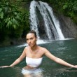 Brunette bathing near a waterfall - Stock Photo
