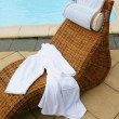 Stock Photo: Wicker sunlounger by pool
