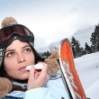 Stock Photo: Skier applying lip salve