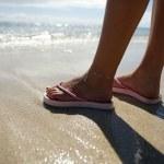 Close-up woman standing on a beach wearing flip-flops — Stock Photo
