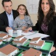 Stock Photo: Architect presenting model housing to a potential client and his daughter