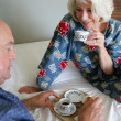 Senior couple having breakfast in bed — Stock Photo