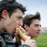 Teenage boy eating sandwich outdoors — Stock Photo