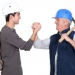 Builder shaking hands with young apprentice — Stock Photo