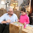 Stock Photo: Little girl playing cards with her grandfather