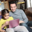 Family sat on the sofa with a laptop — Foto Stock