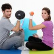 图库照片: Couple lifting weights