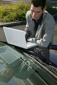 Businessman resting a laptop on his car bonnet — Stock Photo