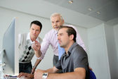 Three business colleagues gathered around computer — Stock Photo