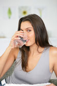 Brunette drinking glass of water — Stock Photo