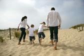 Famiglia camminando lungo una spiaggia di sabbia — Foto Stock
