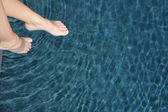 Woman dipping her feet in the swimming pool — Stock Photo