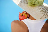 Woman wearing summer hat and holding an apple — Stock Photo